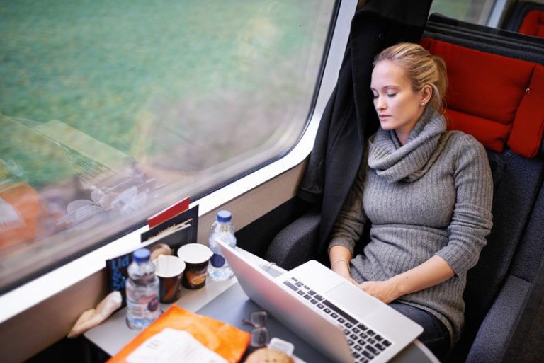 Picture of young professional women travelling on the train asleep with laptop open on the table