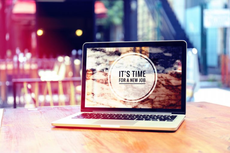 "Open laptop sitting on a desk with ""It's Time for a New Job"" written on the screen. The background is a blurred city landscape."