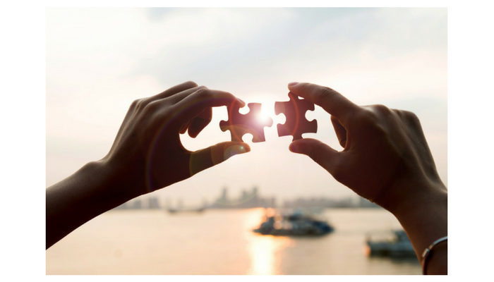 Image of two hands holding matching jigsaw puzzles into the sunset, signifying future plans.